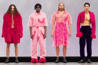 A group of models on the runway for the Liverpool John Moores University Graduate Fashion Week 2019 runway show wearing pink feminine pieces designed for men