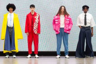 A group of models on the runway for the Liverpool John Moores University Graduate Fashion Week 2019 runway show wearing basic simple oversized pieces in block primary colours