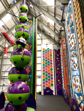 Bo climbing the most difficult wall at the new Clip n' Climb attraction at Wicksteed Park in Kettering. This wall features under and overhang sections.