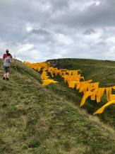 A large scale temporary art installation by Steve Messam occupies Bales Hush in Upper Teesdale in County Durham for 17 days over Summer 2019 photographed here by Pixie Tenenbaum for Fashion Voyeur. Large saffron coloured sails fill a natural gouge in the landscape