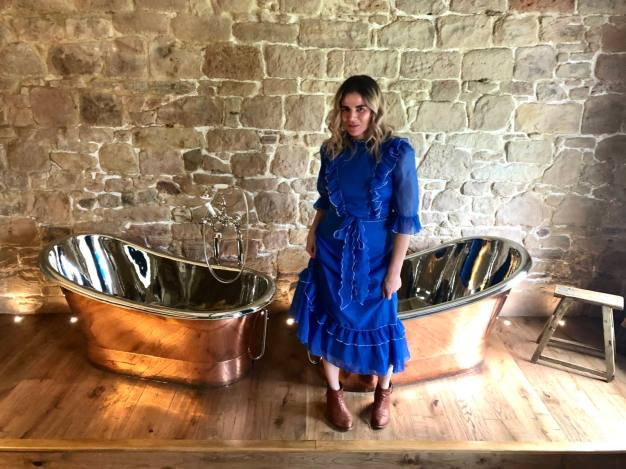 Pixie Tenenbaum wearing a cerulean blue midi vintage prairie dress in the Muckle Hoose Suite at Beadnell Towers Hotel