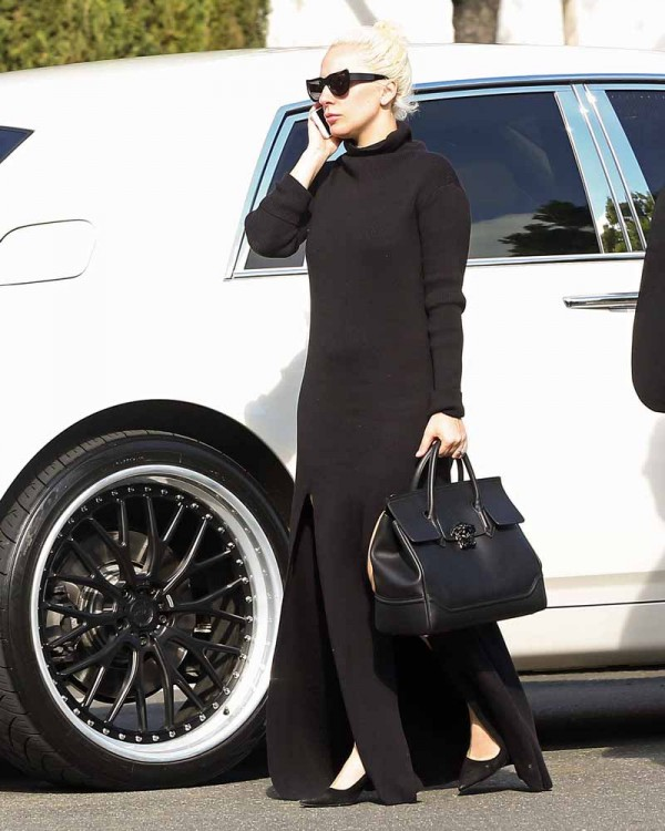 JANUARY 10, 2016: LADY GAGA IS SPOTTED WEARING A LONG TURTLENECK DRESS AND CARRYING A VERSACE PALAZZO BAG AS SHE COMES OUT OF WHITE TOWN CAR TO PREPARE FOR THE 73RD ANNUAL GOLDEN GLOBES IN LOS ANGELES, CA. SHE IS NOMINATED FOR BEST ACTRESS IN A MINISERIES OR MOTION PICTURE FOR TELEVISION FOR HER ROLE IN 'AMERICAN HORROR STORY: HOTEL'. CANDID, EXCLUSIVE, SUNGLASSES, TURTLENECK, DRESS, LONG DRESS, SLIT, BLACK PURSE, LEATHER PURSE, BLACK, HIGH HEELS, BLACK HEELS