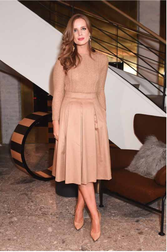 Alex Merrell in Max Mara camel sweater and camel skirt.