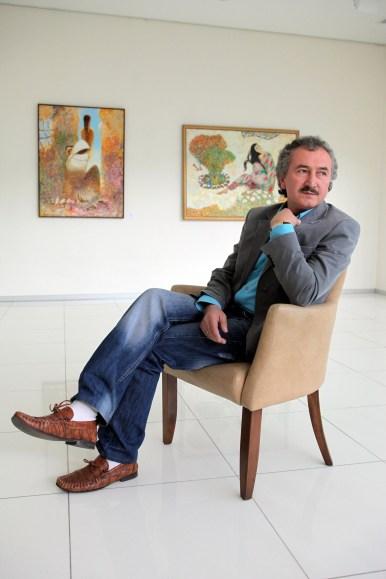 Painter Akmal Nur in front of one of his paintings