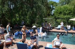 Guests mingle around the pool at the Solid & Striped BBQ