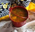 close up of rasam recipe in a red bucket