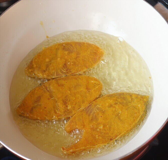 frying fish in oil in a white pan