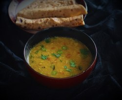 moong dal recipe in a bowl with chapati in the background