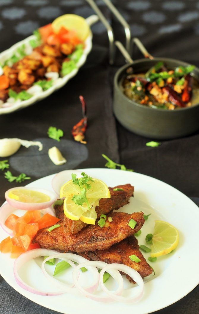 pomfret fish fry recipe served in white plate along with onion rings, lemon wedges