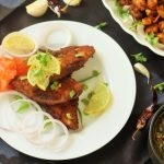 pomfret fish fry recipe served in white plate garnished with onion rings, coriander leaves, and lemon wedges