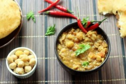 chana masala served in a black bowl garnished with coriander leaves