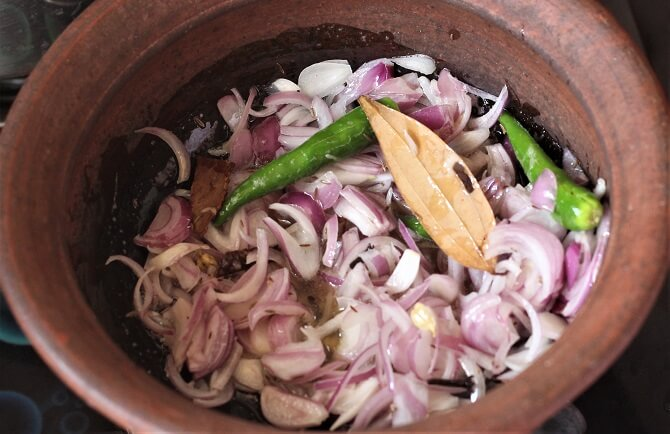 frying onion, garam masala, green chili in ghee for making anda biryani
