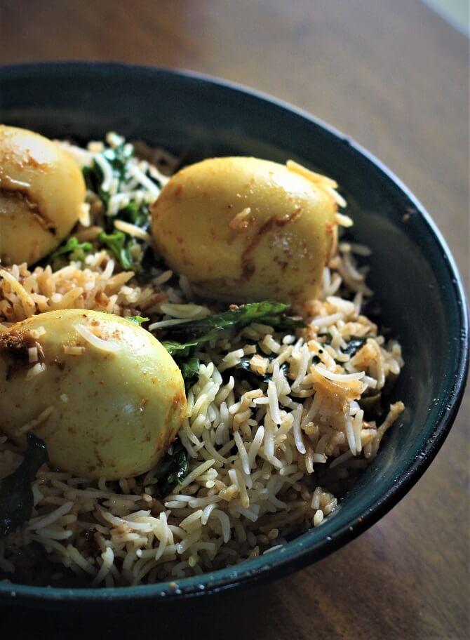hyderabadi anda biryani recipe served with boiled eggs in a blue bowl