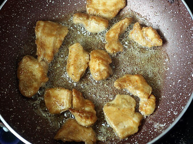frying the chicken pieces in oil in a pink pan