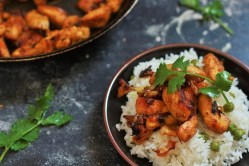 tawa chicken recipe on top of rice garnished with coriander leaves