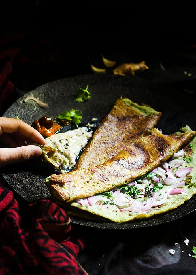 taking a bite of the andhra pesarattu dosa recipe
