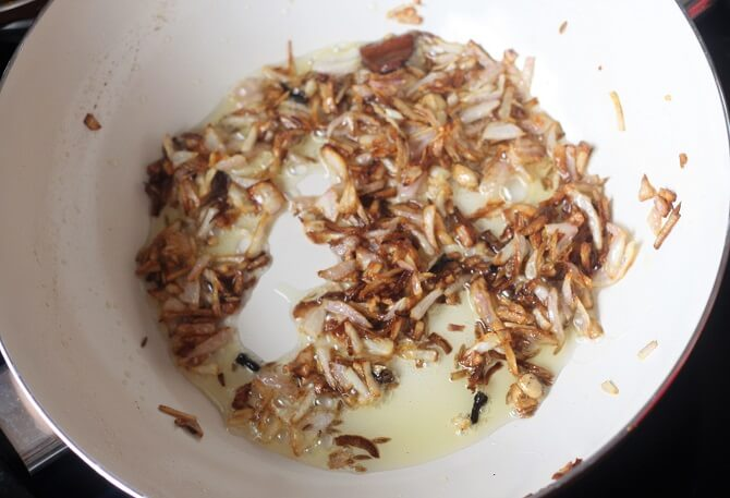 browning onion for making paneer lababdar in white pan