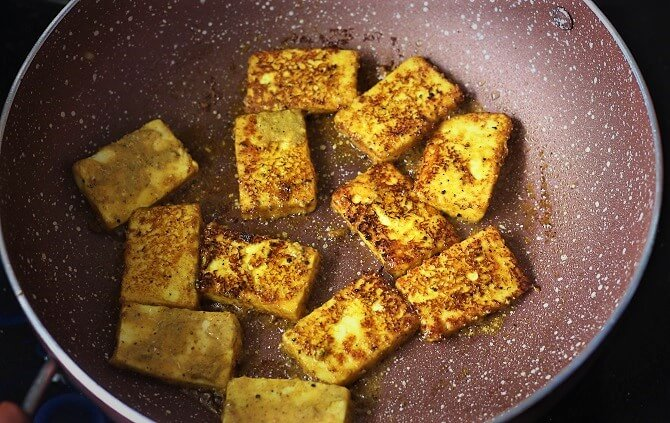 cooking paneer in a pink pan for paneer fry recipe