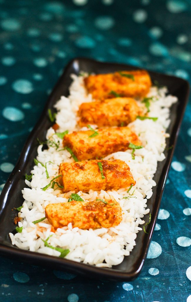 paneer fry recipe placed upon white rice on a long black plate