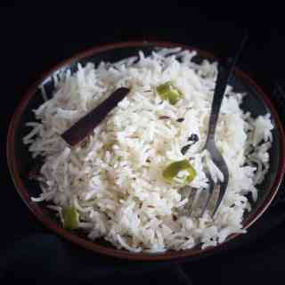 jeera rice recipe in a black plate with a fork