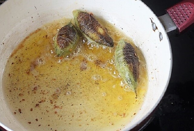 bharwa karela fry getting cooked in a white pan