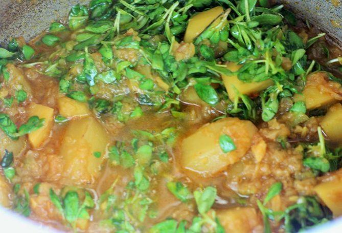 methi leaves in half cooked potatoes