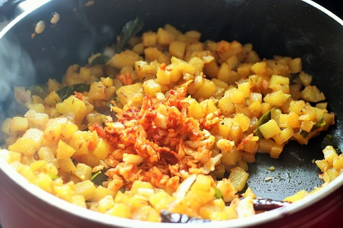 adding crushed garlic and chili to potato