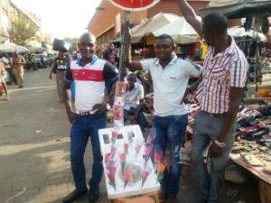 M. Dao Souleymane (Au milieu) devant son étalage de fleurs St Valentin en compagnie de nouveau acheteurs