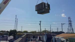 Comfort Time using a crane to lift an air conditioner onto a roof