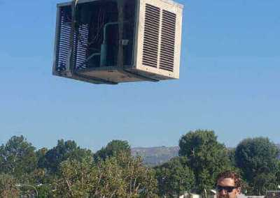 Comfort Time lifting an Air Conditioning unit onto the roof of a customer