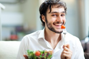 Happy man eating a salad