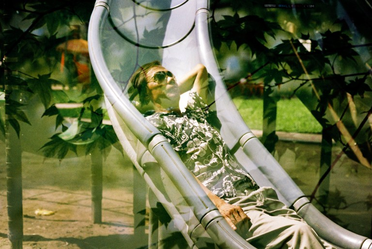 My father was lying on the children's slide under the sunshine in Lenin park, Hanoi, is overload by leafs from the garden in Thu Le zoo in Hanoi, Vietnam on August 2013