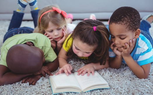 Image of four children sharing one book.