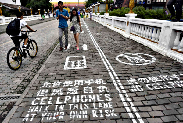 "A man rides his bicycle as people walk on the ""first mobile phone sidewalk in China"", which was recently installed at a tourism area in Chongqing municipality...A man rides his bicycle as people walk on the ""first mobile phone sidewalk in China"", which was recently installed at a tourism area in Chongqing municipality, September 13, 2014. The mobile phone sidewalk in Chongqing was divided into two sides -- one was written with ""Cellphones walk in this lane at your own risk"" while the other with ""No cellphones"", as an attempt to reduce pedestrian incidents, local media reported. Picture taken September 13, 2014. REUTERS/China Daily (CHINA - Tags: SOCIETY SCIENCE TECHNOLOGY) CHINA OUT. NO COMMERCIAL OR EDITORIAL SALES IN CHINA"