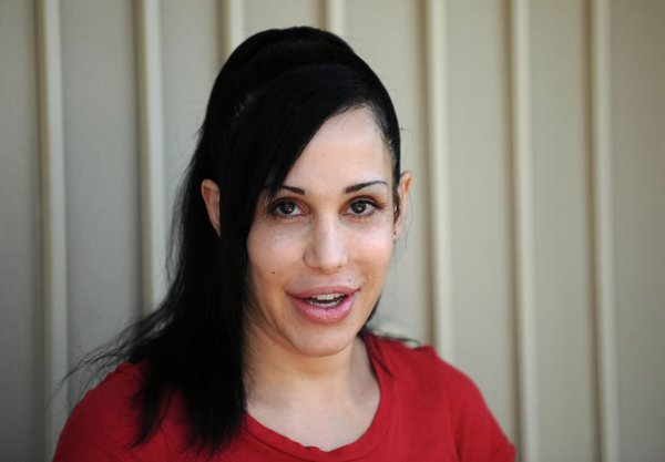 """""""Octomom"""" Nadya Suleman poses for photographers in front of her home in La Habra, California on May 19, 2010. Suleman who has been facing possible home forclosure agreed to display a banner for Peta who offered to give her $5,000 USDand a month's worth of free veggie dogs and veggie burgers. AFP PHOTO / GABRIEL BOUYS (Photo credit should read GABRIEL BOUYS/AFP/Getty Images) ** TCN OUT ** ORG XMIT: 99302088"""