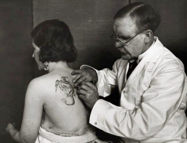 ca. 1930, England, UK --- Tattoo Artist Tattoos Woman --- Image by © E.O. Hoppé/CORBIS