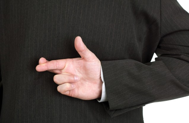 Businessman with his fingers crossed behind his back - concept for good luck or dishonesty; Shutterstock ID 41914792; PO: aol; Job: production; Client: drone