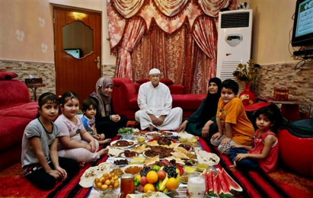 This Sunday, July 6, 2014 photo, shows an Iraqi family waiting to break their fast during the hold month of Ramadan in Basra, Iraq. For the millions of Muslims abstaining from food and drink from sunrise to sunset every day during Islam's holiest month of Ramadan, that first sip of water after a grueling fast is by far the most anticipated moment of the day. (AP Photo/ Nabil al-Jurani)