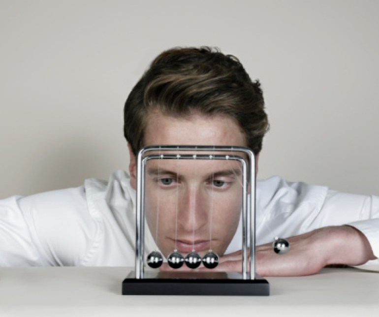 Businessman looking closely at Newton's Cradle