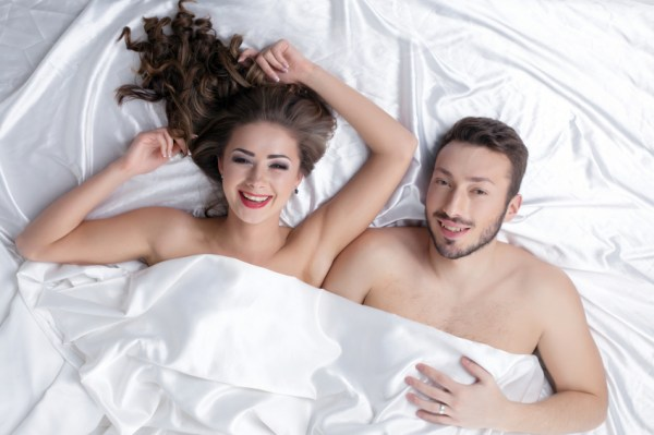 Cheerful heterosexual couple posing in bed, close-up