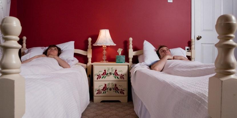 Young couple lying awake in single beds