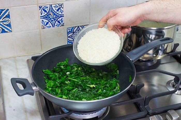 Versiamo in una pentola capiente un filo d'olio, facciamolo riscaldare, quindi aggiungiamo il cipollotto tritato e facciamolo imbiondire. Pronto il soffritto, aggiungiamo gli spinaci precedentemente lavati e tritati grossolanamente e cuociamoli un paio di minuti o comunque il tempo necessario per farli appassire. Cotti gli spinaci, aggiungiamo il riso e tostiamolo a fiamma vivace per qualche minuto, aggiustando con sale e pepe secondo i nostri gusti. Sfumiamo adesso con il vino bianco.