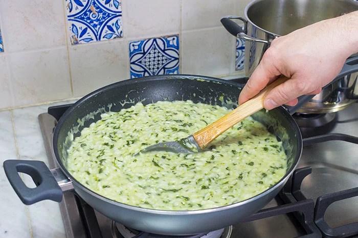 Cotto il riso al dente, spegniamo il fuoco, aggiungiamo il latte e il formaggio grattugiato e mantechiamo mescolando energicamente. Volendo potremmo fermarci a questo punto della ricetta e gustare il risotto in semplicità, ma dato che dobbiamo continuare la cottura in forno, vi consiglio di realizzare un risotto molto al dente e di lasciare il fondo molto