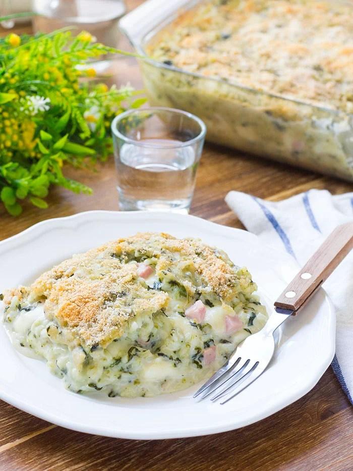Ecco lo sformato di riso agli spinaci servito in tavola! Al suo ripieno filante di mozzarella e besciamella nessuno saprà resistere!