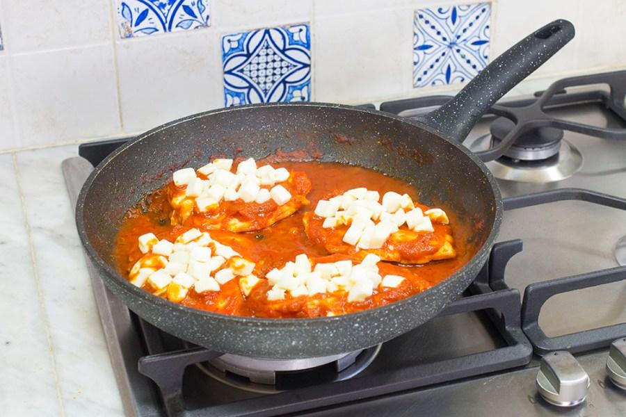 Come ultimo passaggio, ricopriamo le fette di pollo con la mozzarella tagliata a cubetti, rimettiamo il coperchio e cuociamo il tempo necessario per far fondere il formaggio.