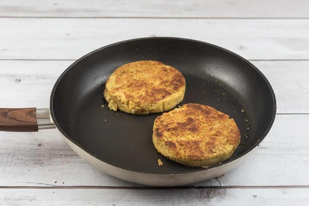 Cuociamo i burger di ceci in una padella antiaderente fino a quando saranno dorati e si sarà formata una crosticina. Facciamoli raffreddare per una decina di minuti.