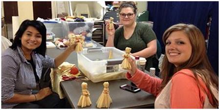Faulkner County Museum interns work on corn husk dolls