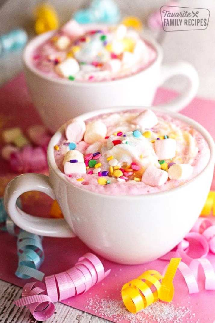 Two white mugs filled with Unicorn Hot Chocolate topped with mini marshmallows and sprinkles