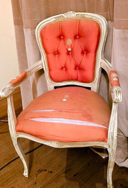 French silk-upholstered chair, showing damage to its seat area