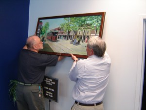 Photo of BJ Bjork and Frank Quinn hanging a Homer White painting on loan